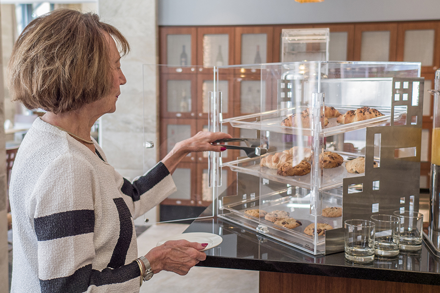 woman selecting pastries from display