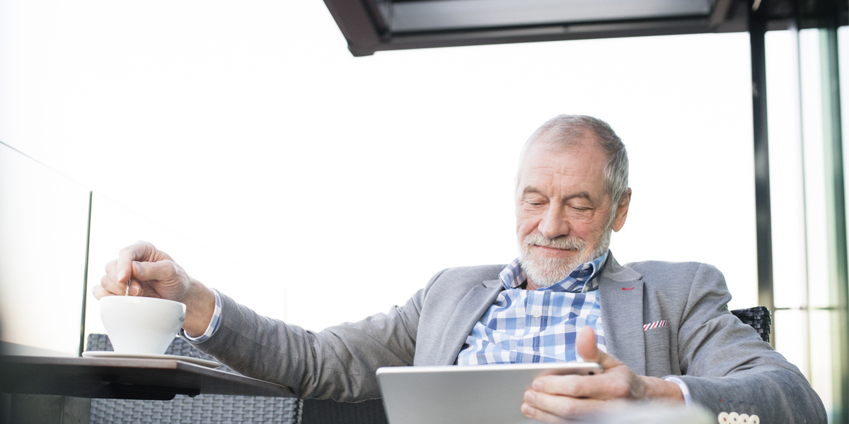 Senior man on tablet while drinking coffee