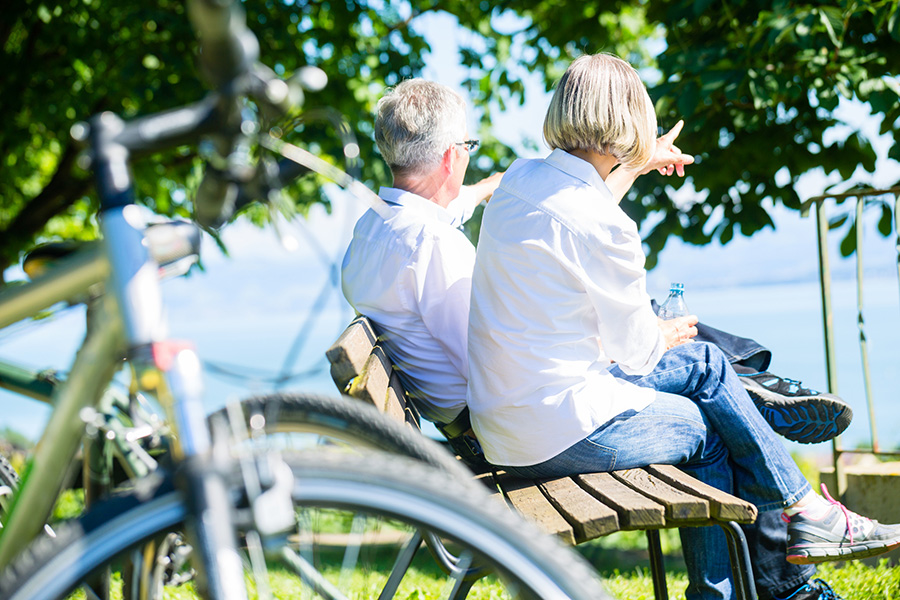Couple sits on bench after biking